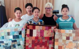 Helping young mothers-to-be make their first baby quilt from reclaimed fabrics.
